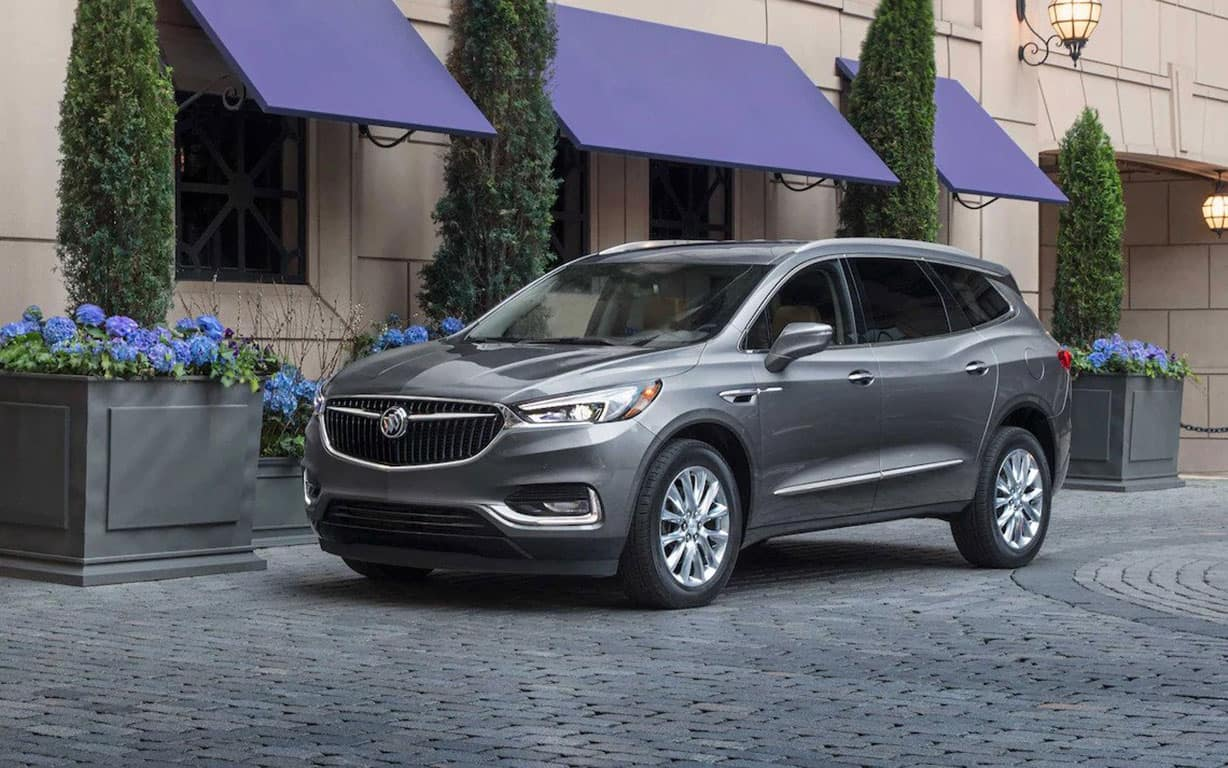 2021 Buick Enclave Premium (1SN) in Satin Steel Metallic, shown with 20' polished aluminum wheels (SQ7). Vehicle parked in front of upscale hotel. Purple awnings, blue hydrangeas.