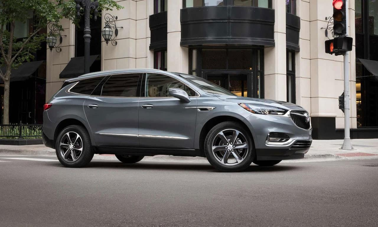 2021 Buick Enclave Premium (1SN) in Satin Steel Metallic with 20 inches ultra-bright machine-faced aluminum wheel with Satin Graphite pockets (S1T) (dealer-installed accessory), vehicle on city street in front of retail storefront
