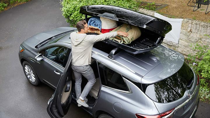 2021 Buick Enclave Premium (1SN) in Satin Steel Metallic with available 20 inch polished aluminum (SQ7) wheels. Image highlights overhead view of accessory cargo carrier. Driver side rear door open with lifestyle, talent, man putting props in cargo carrier.