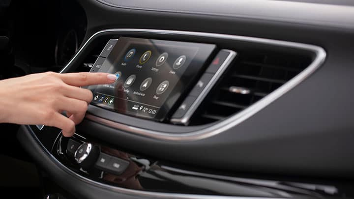 Finger on Buick Infotainment color touchscreen.
