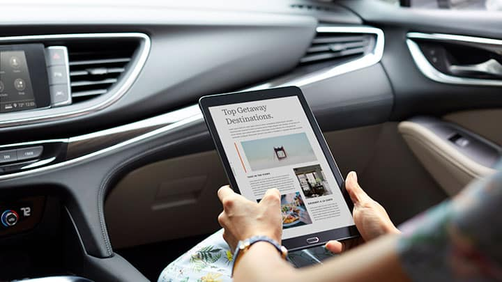 2021 Buick Enclave Premium (1SN) interior in Shale with Ebony accents. Passenger side front seat with lifestyle, talent, woman holding tablet. Wi-fi compatibility. Closeup of tablet features Top Getaway Destinations