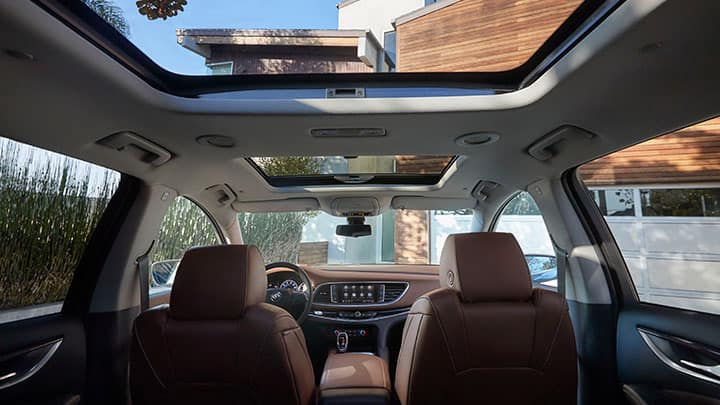 2021 Buick Enclave Avenir (1SP) interior. View from rear seat of Chestnut (HHH) perforated leather-appointed seats with Ebony accents. Featuring power moon-roof with rear fixed skylight. Contemporary home seen through windows, moonroof and skylight