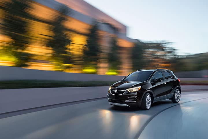 2021 Buick Encore Preferred with Safety Package II in Ebony Twilight Metallic; 3/4 Drivers side Front; Road shot/motion; At dusk/dawn with Illuminated LED Headlamps