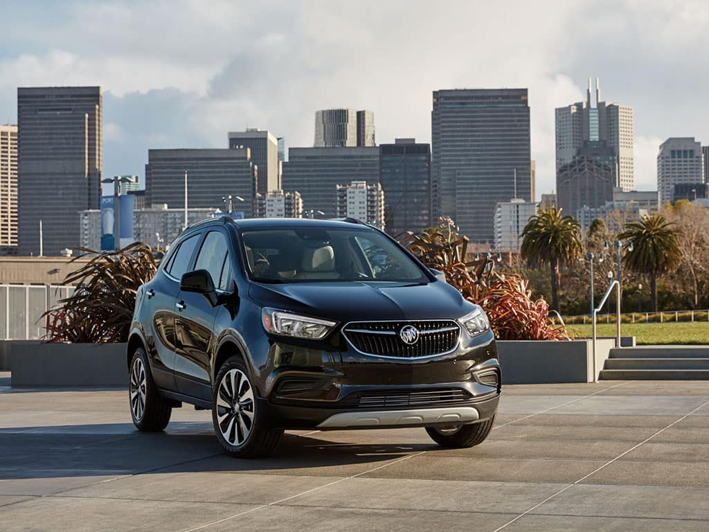 """2021 Buick Encore Preferred (1SB) in Ebony Twilight Metallic. Shown with 18"""" 10-spoke aluminum wheels with Technical Gray Finish (RRU). Vehicle parked with city in the background, cement steps, palm trees."""